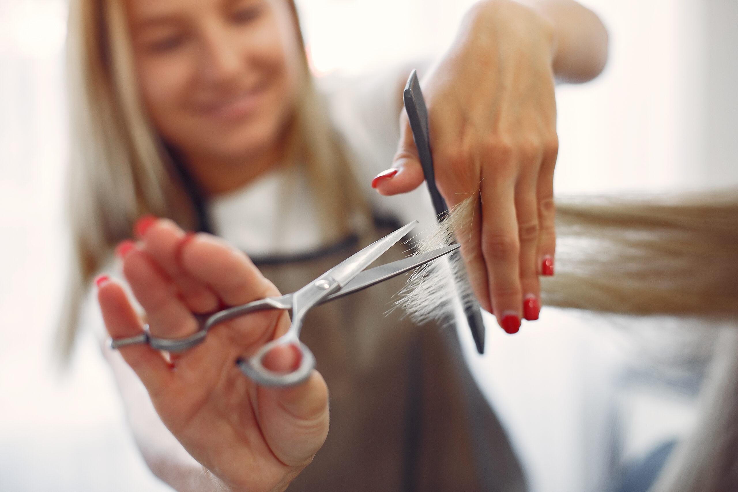 Hairdresser cut hair her client in a hair salon